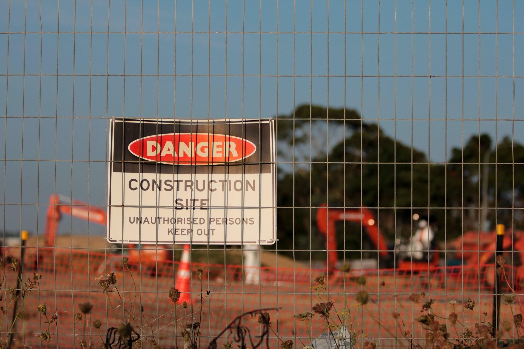 Danger sign behind construction site fence